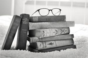 Okulary leżące na stosie starych książek