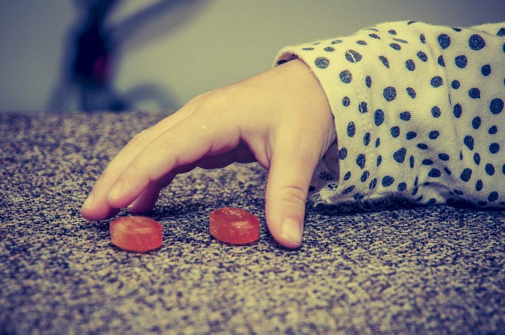 Dłoń dwulatka sięgająca po czerwone cukierki