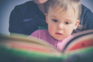 Dziecko czytające książkę z mamą