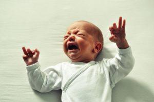 Płaczące dziecko w białych śpioszkach